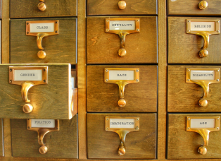 Card catalog with drawers labeled gender, race, disability, class, sexuality, religion, politics, immigration, and age